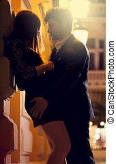 Man and woman kissing at night