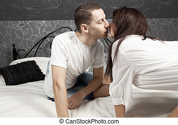 man and woman kissing in the bed
