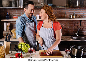 Man and woman laughing while cooking