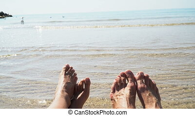 Man and woman legs against the sea on the summer beach, time...