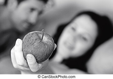 Man and woman lie in bed and the woman holds a red apple....