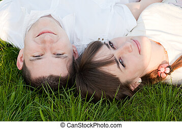 Man and woman lie on the grass