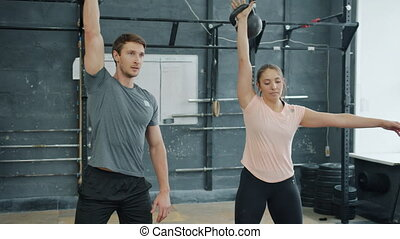 Man and woman lifting kettlebells training in gym together busy with sports exercise