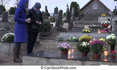 Man and woman light candle with matches on family member grave in cemetery. 4K