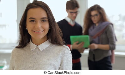Man and woman look at the tablet behind the smiling girl at the office
