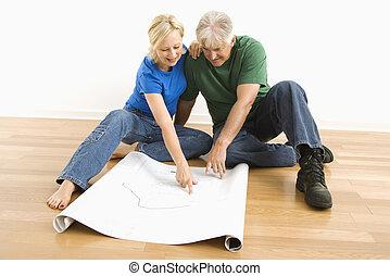 Man and woman looking at blueprints.