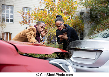 Man And Woman Looking At Smoke Coming Out From Car's Engine After Accident