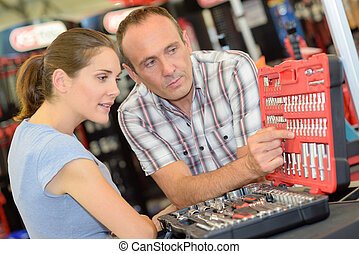 Man and woman looking at case of tool attachments