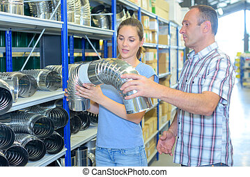Man and woman looking at flexible metal pipe