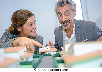 Man and woman looking at model houses