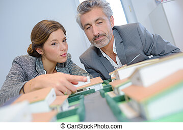 Man and woman looking at model housing development
