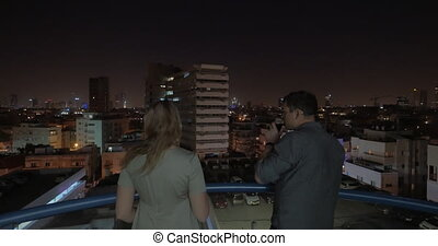 Man and woman looking at night Tel Aviv from the hotel roof,...