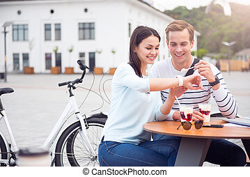 Man and woman looking at smartwatch