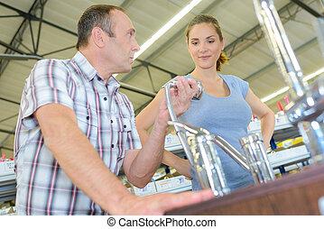 Man and woman looking at taps