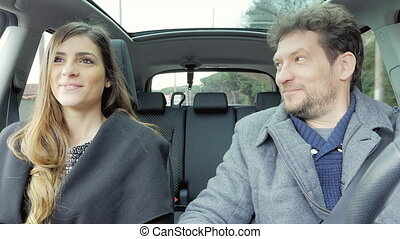 Man and woman looking each other in car talking and laughing while driving