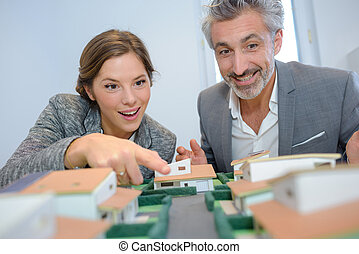 Man and woman looking excitedly at housing model