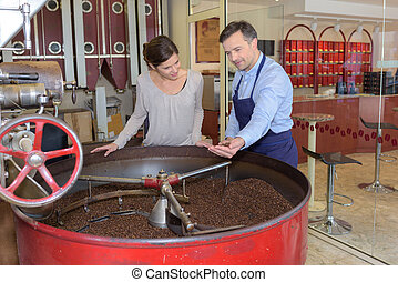Man and woman looking into vat of coffee beans