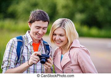 Man and woman looking photos at camera