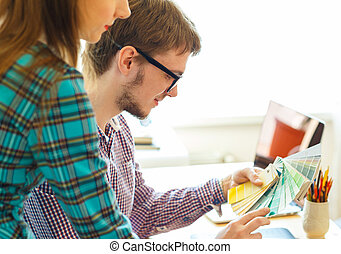 Man and woman looking to a color paint palette at home...