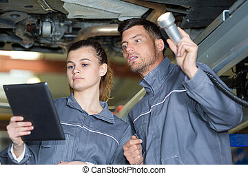 man and woman mechanic examine the underside of a car