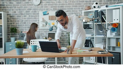 Man and woman mixed race coworkers working with computers in modern office