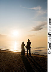 Man and woman near a sea - Youths man and woman stand ashore...