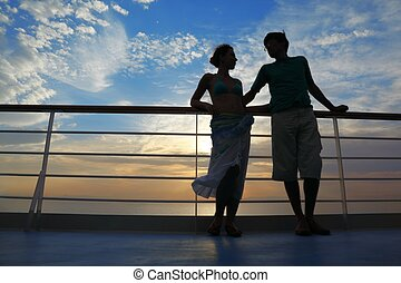 man and woman on deck of cruise ship. man looking at woman and woman looking at man.