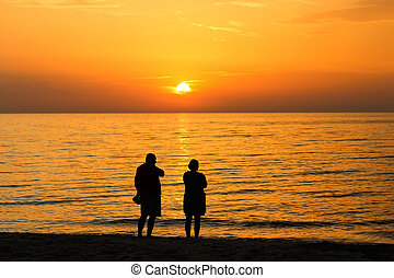 Man and woman on the beach watching the sun set.