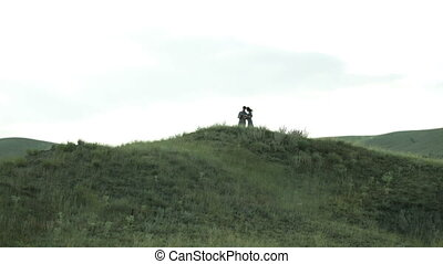 man and woman on the hill watching the pictures
