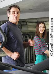 Man and woman on treadmills