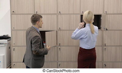 Man and woman open boxes and pick up things in modern...