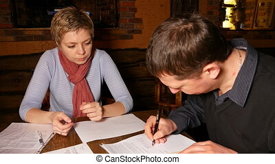 Man and woman partners signing contract in cafe
