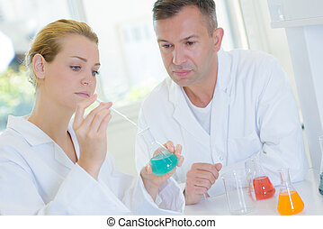 Man and woman performing experiment in laboratory