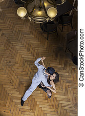 Man And Woman Performing Tango On Hardwood Floor