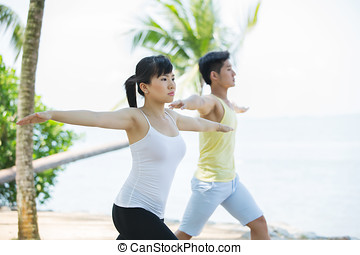 Man and Woman performing yoga.