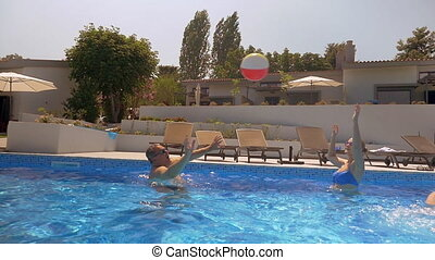 Man and woman playing with ball in the pool
