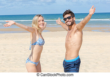 man and woman posing on the beach
