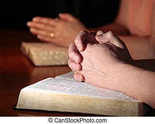 A man and woman (or couple) praying together with their Holy Bibles open under their hands (focus on man's foreground hands).