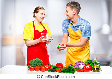man and woman preparing healthy vegetable salad in the kitchen