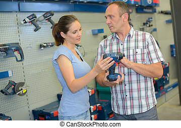Man and woman purchasing power tool