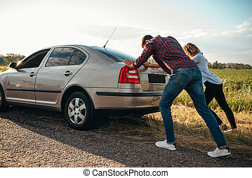Man and woman pushing a broken car, back view - Man and...