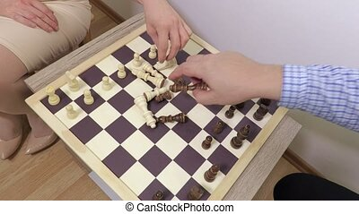Man and woman put chess pieces on chessboard