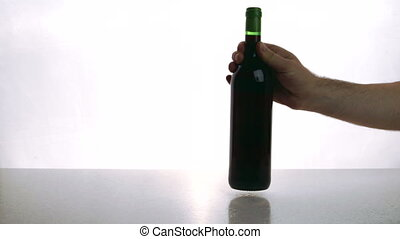 Man and woman put on desk bottle of red wine and glasses...