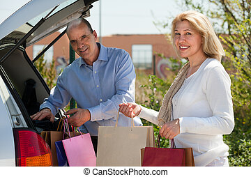 Man and woman putting bags in car trunk