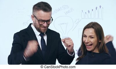 Man and woman rejoice in success and having fun in a modern glass office