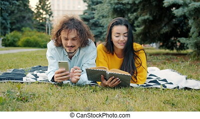 Man and woman relaxing in park using smartphone and reading book talking