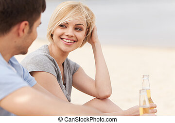 Man and woman relaxing on beach with beer. Happy couple drinking together on beach