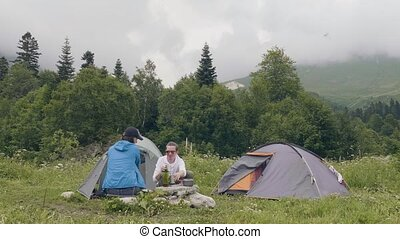 Man and woman resting on camping tent and mountain landscape background