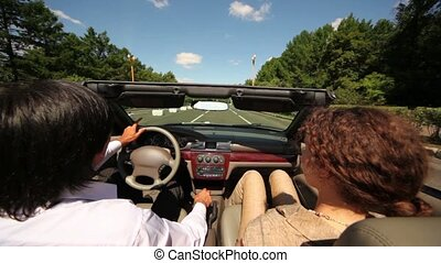 Man and woman ride in cabriolet by asphalt road among trees