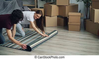 Man and woman rolling out carpet on floor after moving to...